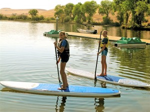On a break from rowing, Jade and Jordan Bennett try out paddle boarding during the 2015 middle school rowing camp held at Forebay Aquatic Center in Oroville. Above: Camp participants practice rowing techniques.